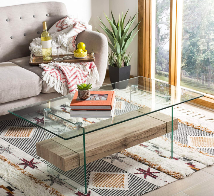Floating glass coffee table on a starfish-printed rug in front of a neutral gray couch with a wine caddy
