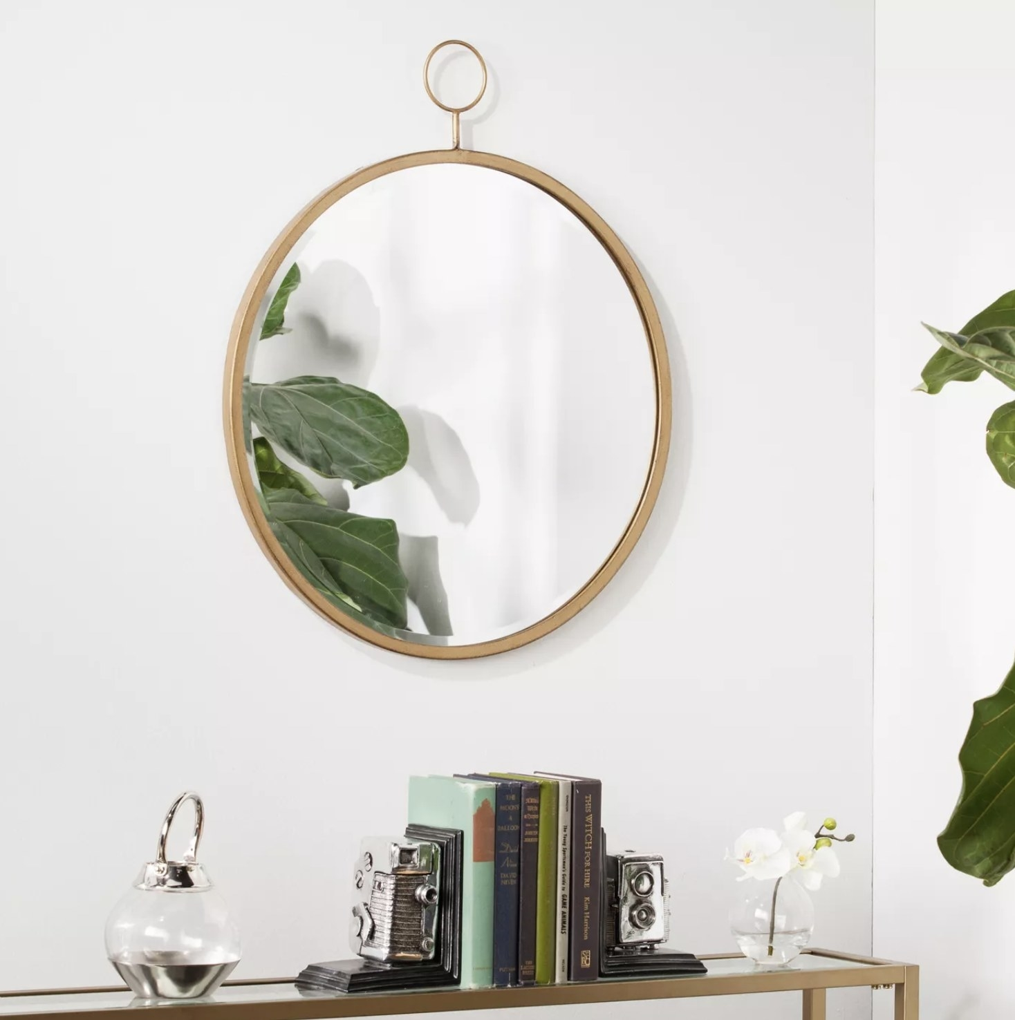 A bronze decorative wall mirror is hung above an entryway table on a white wall