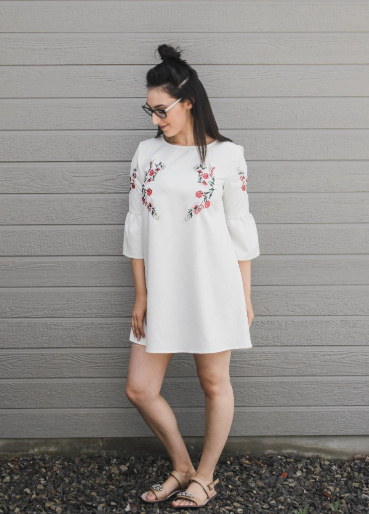 a reviewer in the dress in white with belle sleeves and a subtle floral pattern