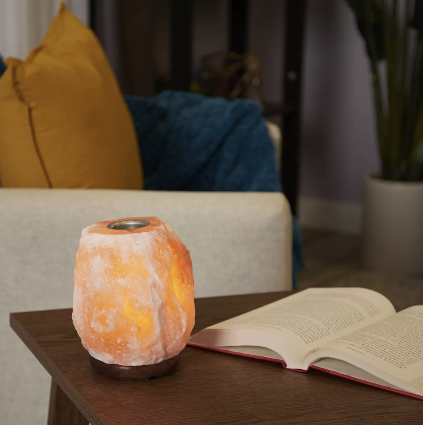 A Himalayan Salt lamp sits on a side table lit up next to a book and couch