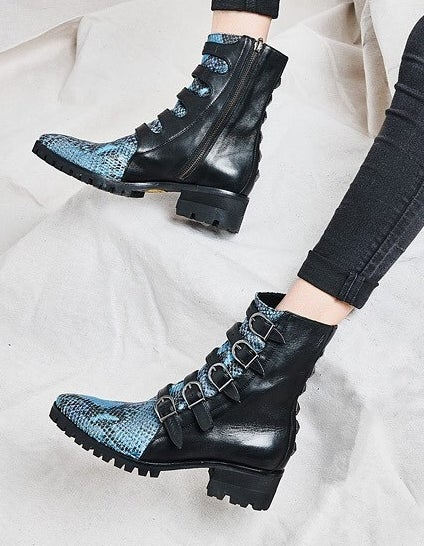 model wearing black five-buckle boots with blue snakeskin detailing