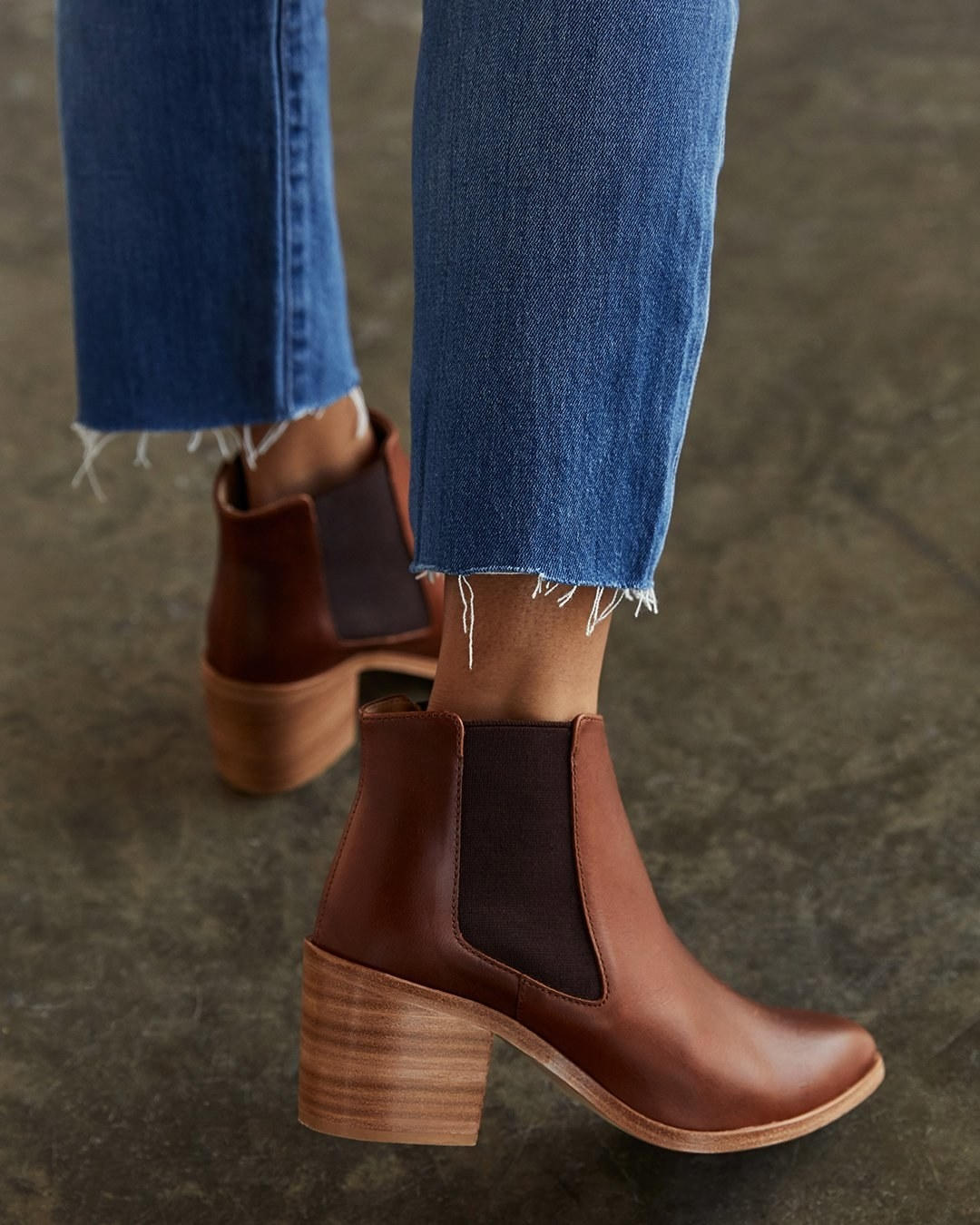 Model wearing the brown boots with lighter brown chunky heel and wide dark brown elastic on each side