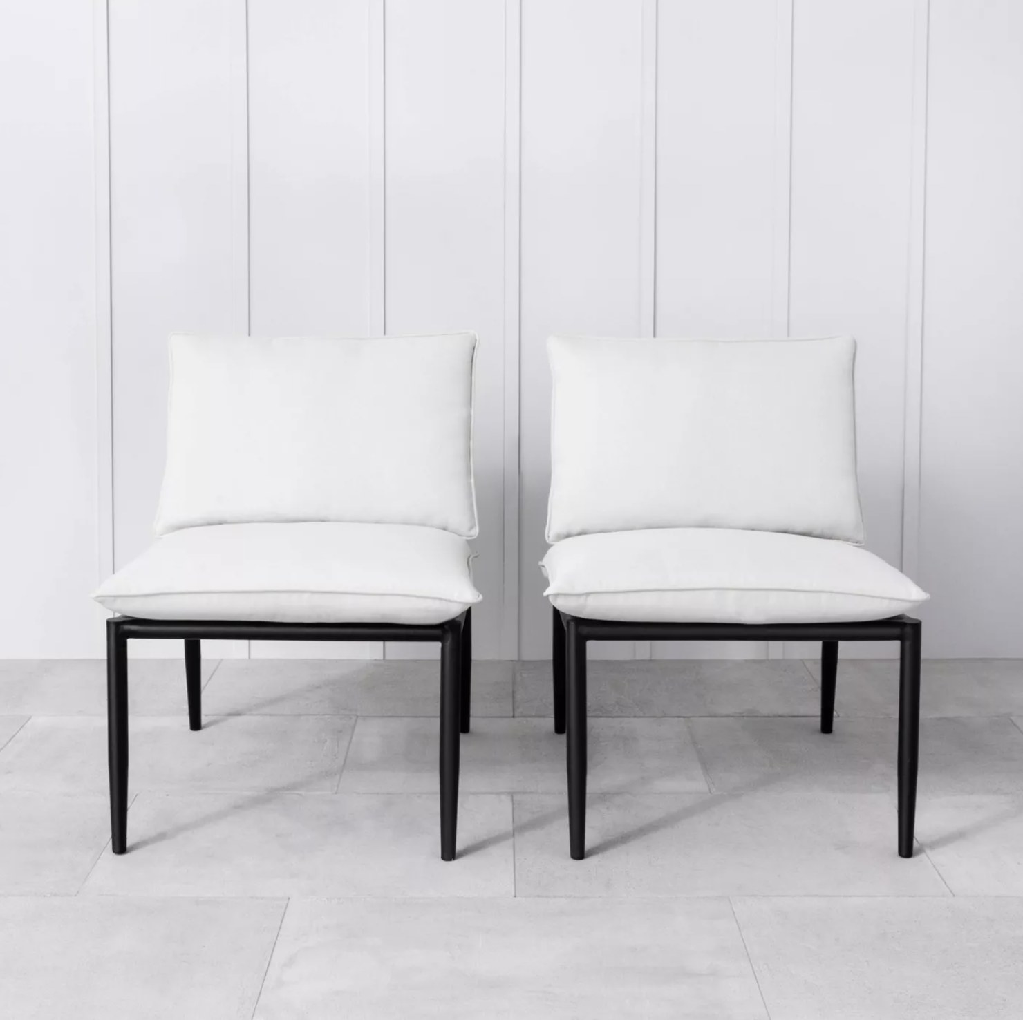 A set of two black patio chairs with white cushions