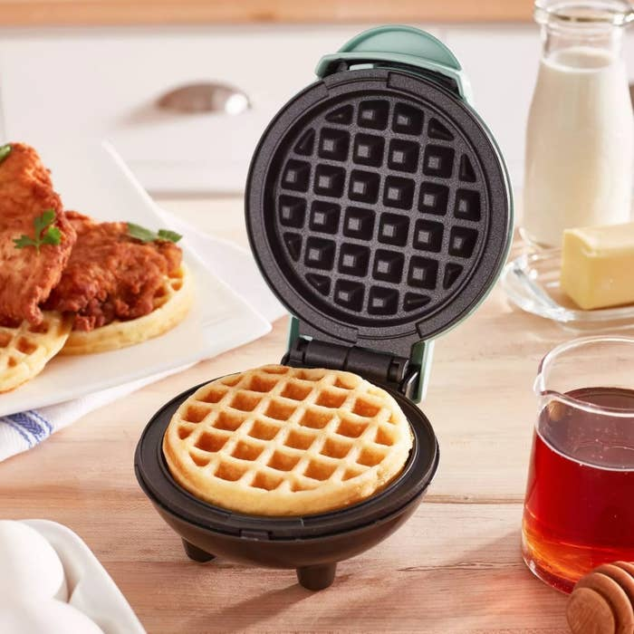 The waffle iron being used to make chicken and waffles