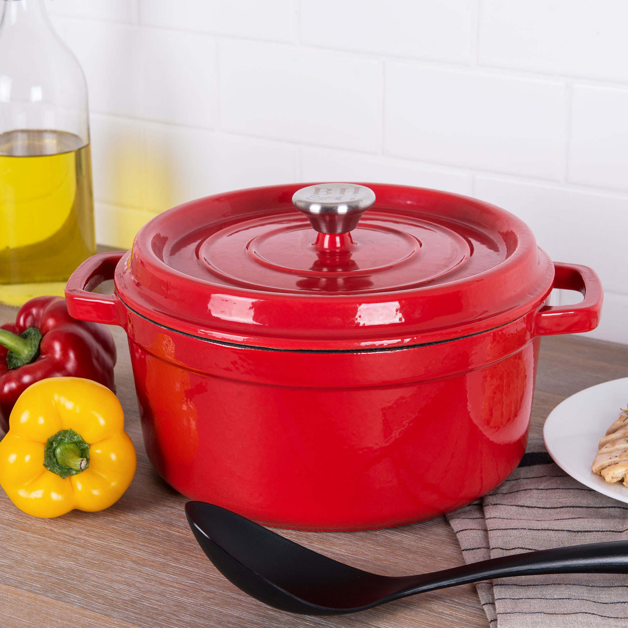 red dutch oven on a counter next to two bell peppers and a spoon
