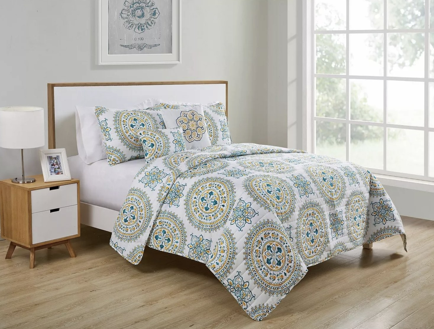 An aqua medallion pattern quilt set on top of a bed in a bedroom