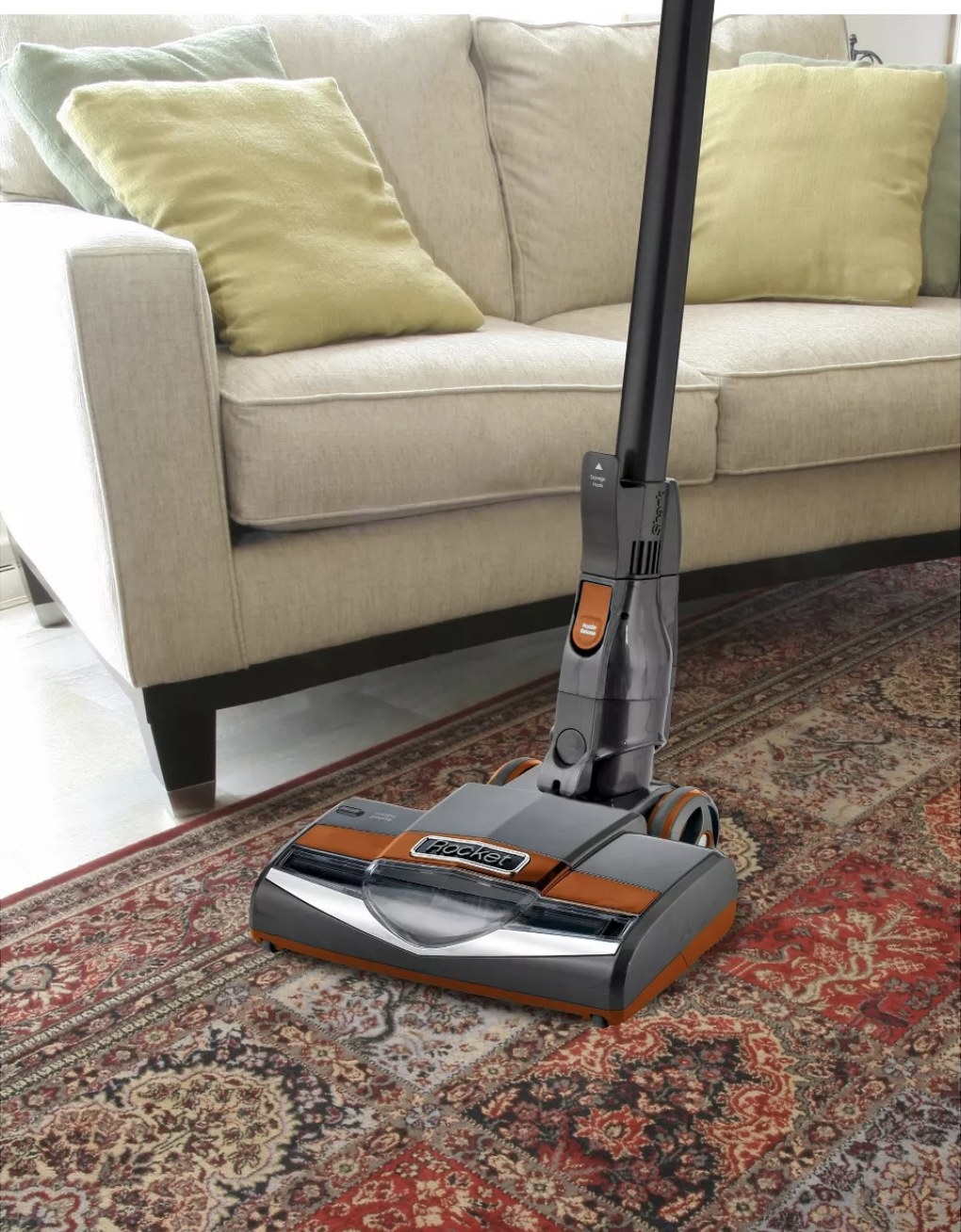 A Shark Rocket ultra-light vacuum is vacuuming a rug next to a couch