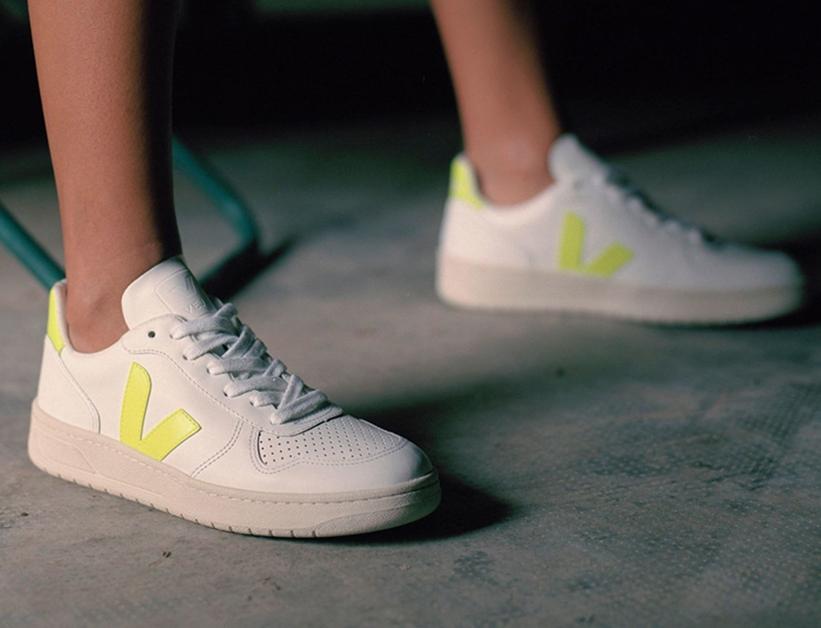 model wearing white sneakers with neon yellow detailing