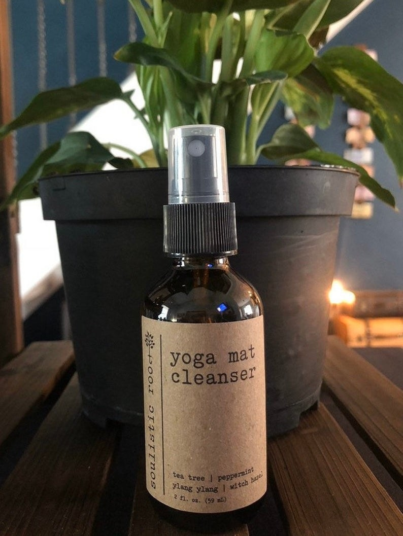 Brown spray bottle of yoga mat cleanser with a brown paper label