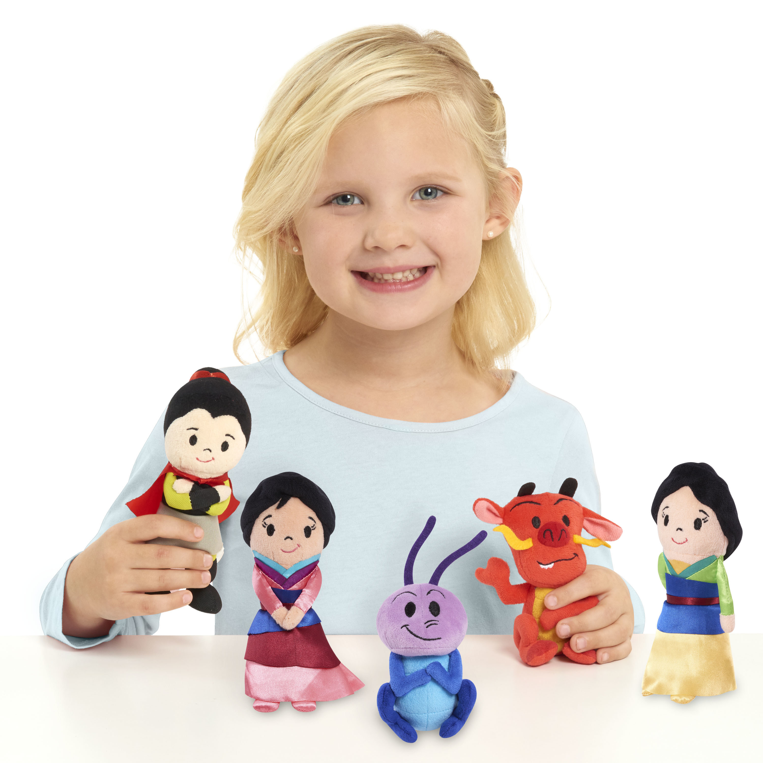 kid playing with five plush dolls from the disney movie Mulan