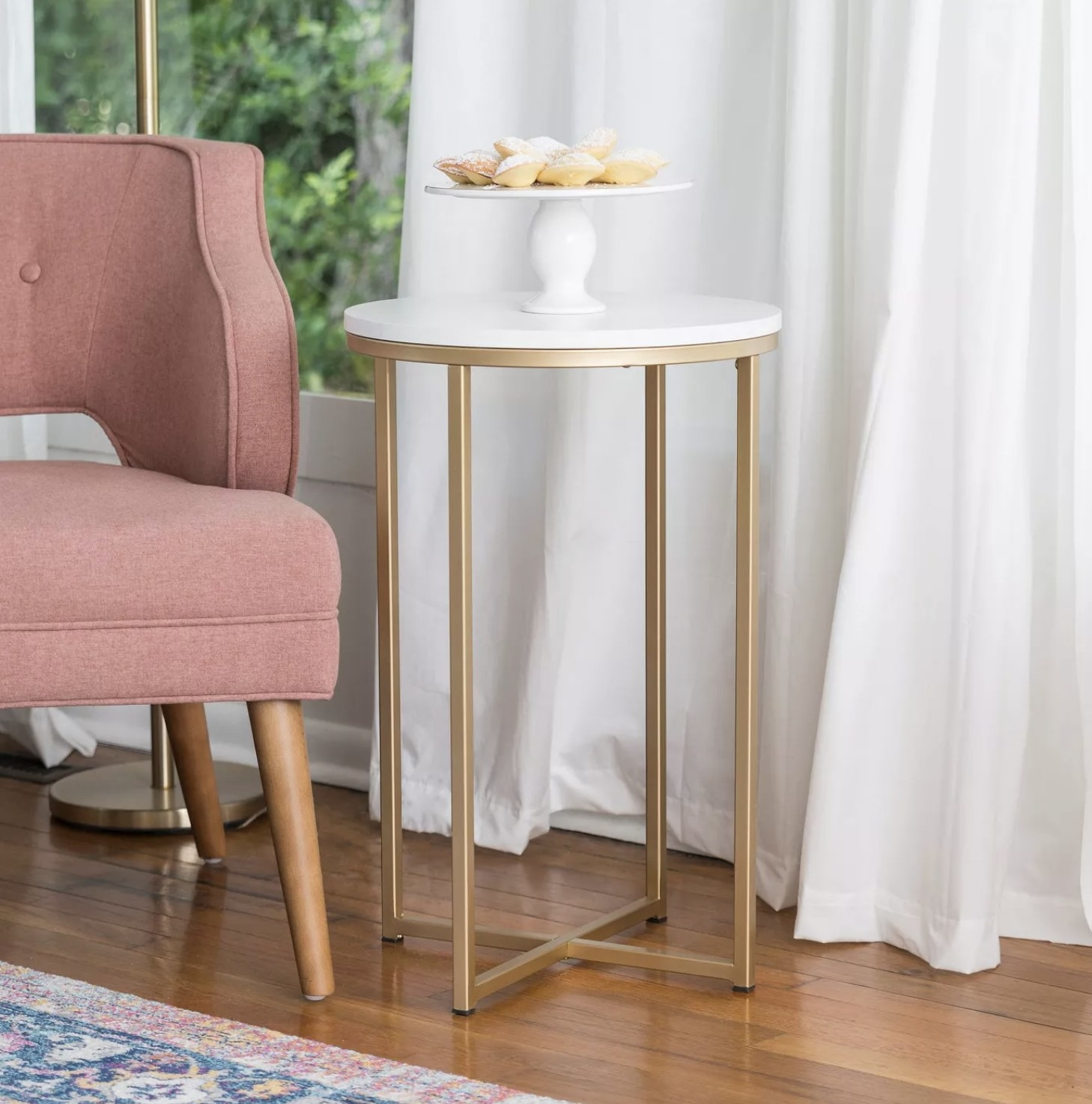 A gold chrome side table with a white tabletop in a living room