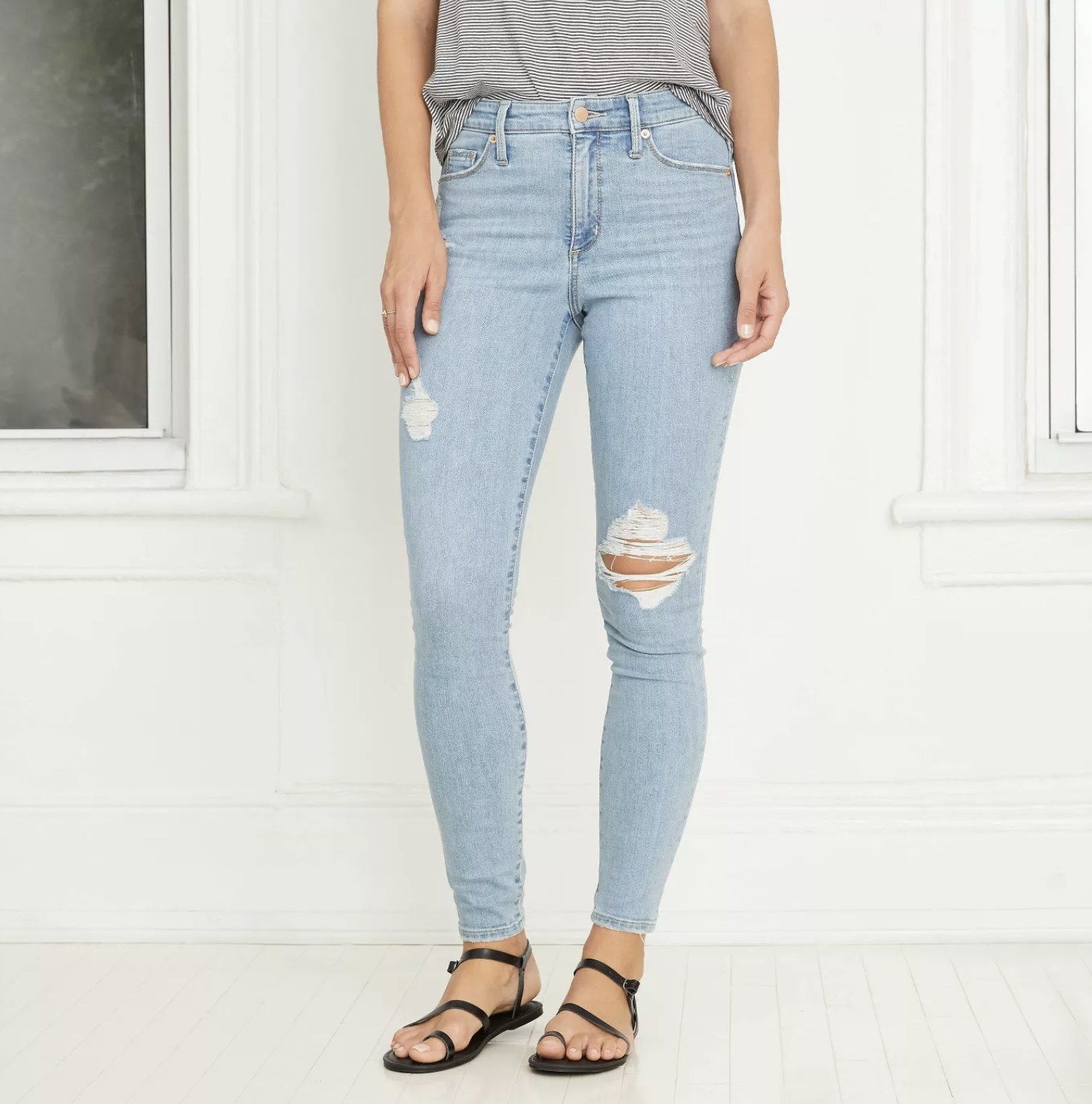 Model is wearing light wash super high-rise skinny jeans and black sandals