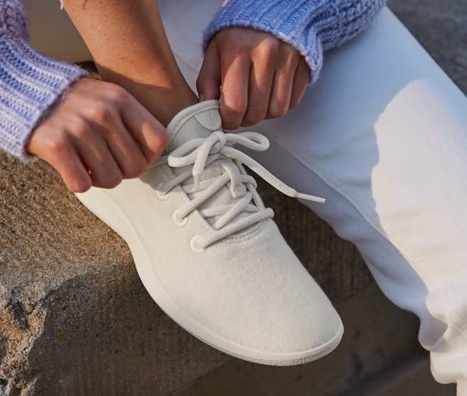 Model wearing the sneakers with thicker fabric in white, with white soles and laces.