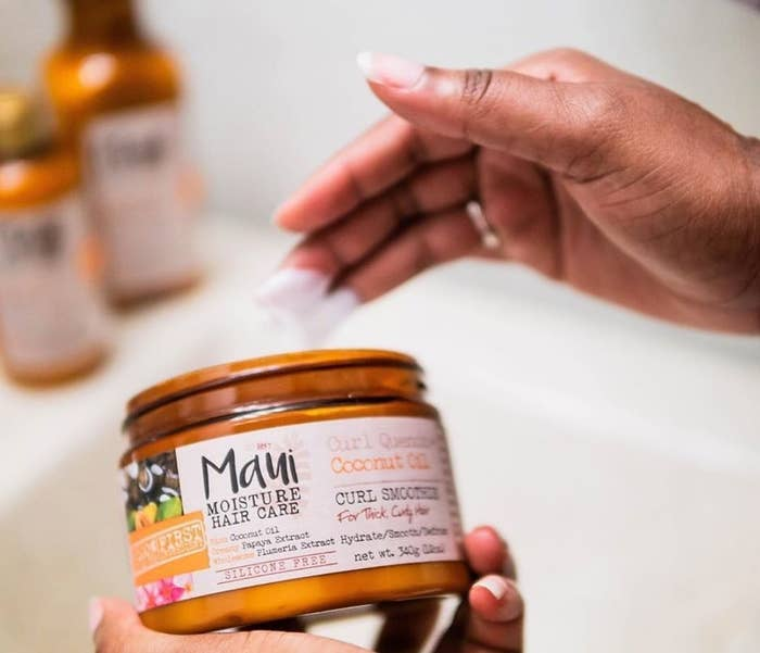 A person holding the jar of maui moisture