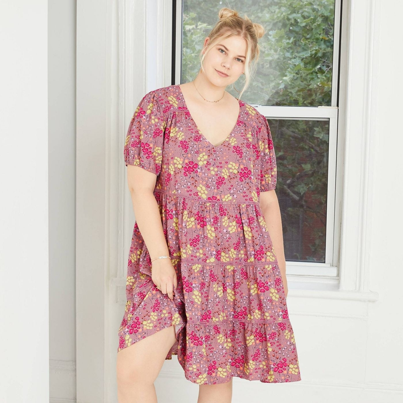 A model wearing the short-sleeve pink and yellow floral dress that hits just above the knee