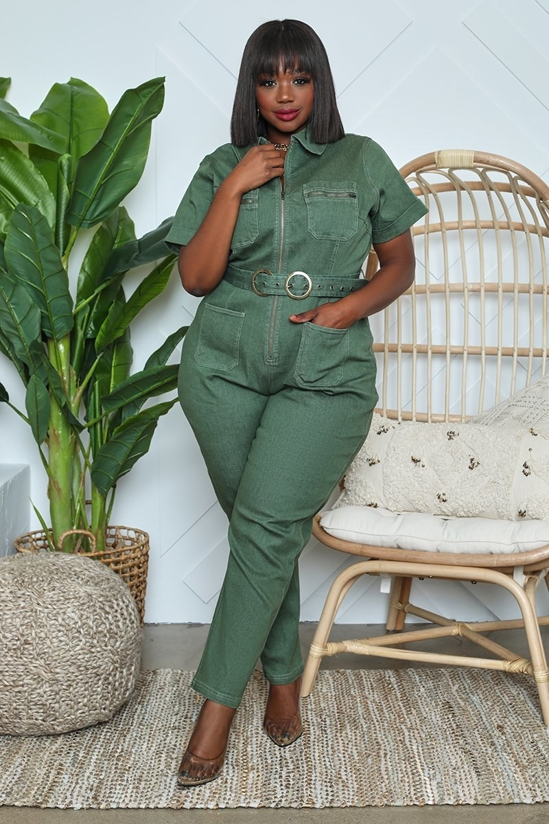 A model wearing the short-sleeve, collared, olive green jumpsuit with their hand in one of the pockets