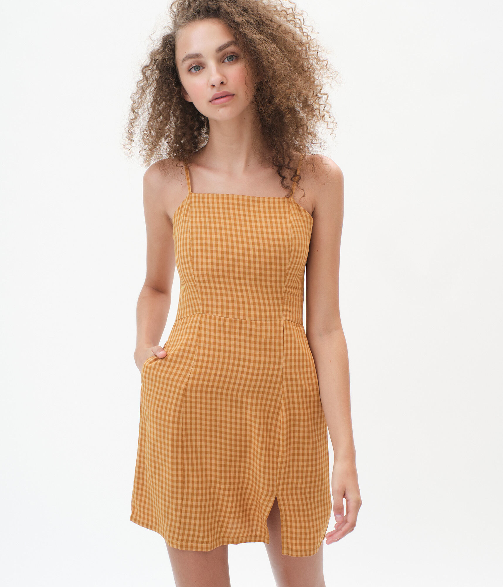 a model in a yellow gingham print mini dress with her hand in the pocket