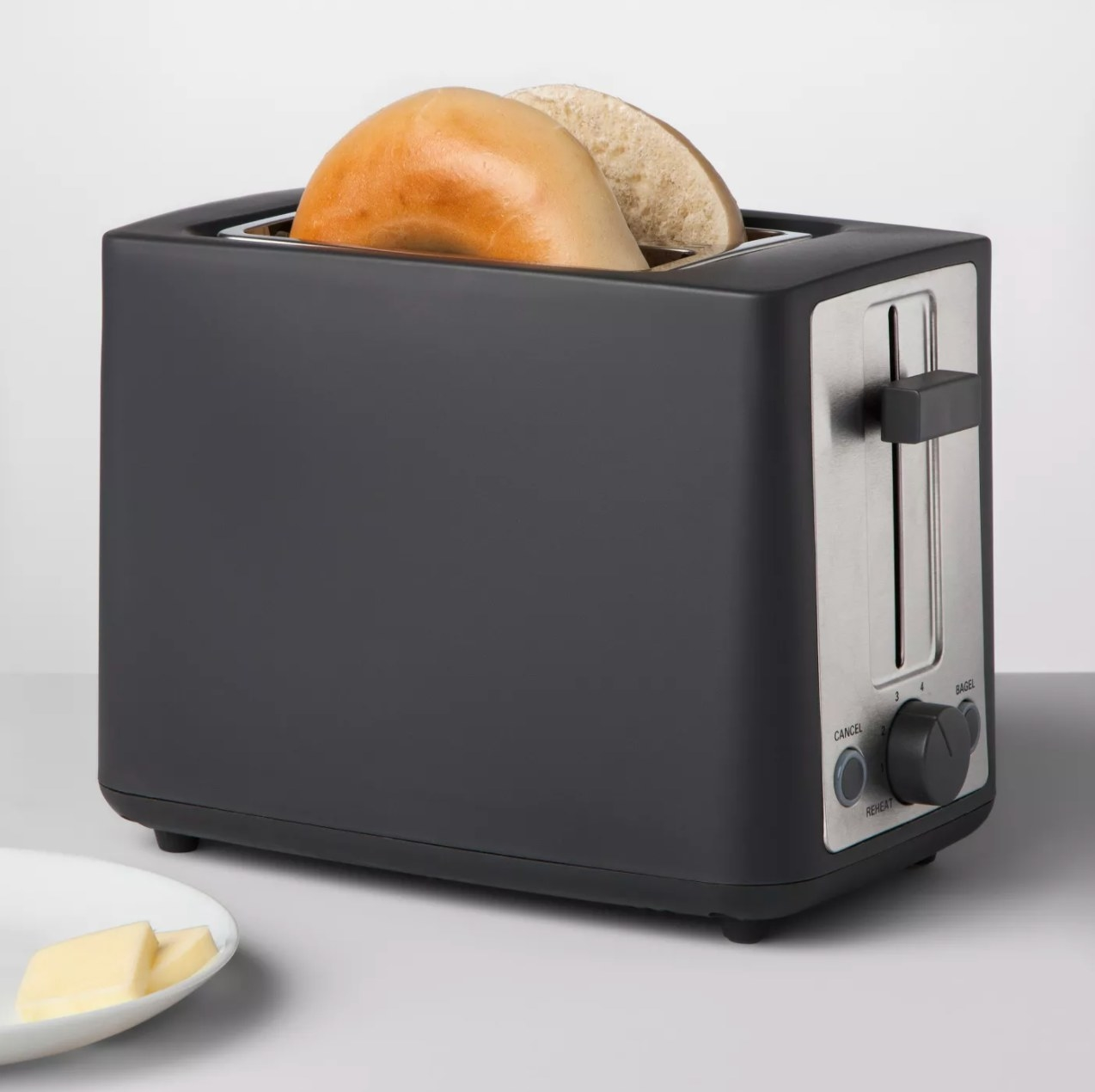 The toaster heating up a bagel with a side of butter