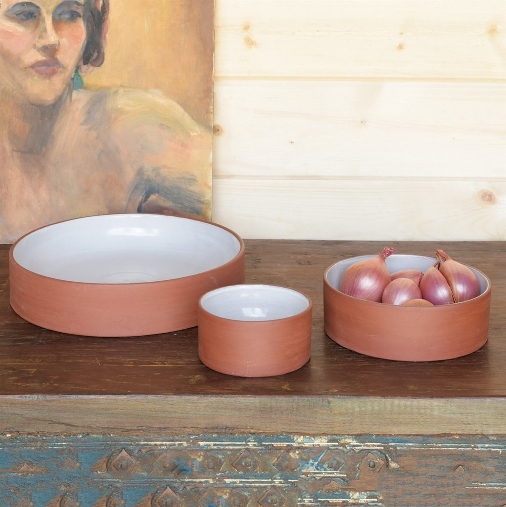 three sizes of flat-bottom vertical wall shallow bowls that are terracotta on the outside and white on the inside with onions in one