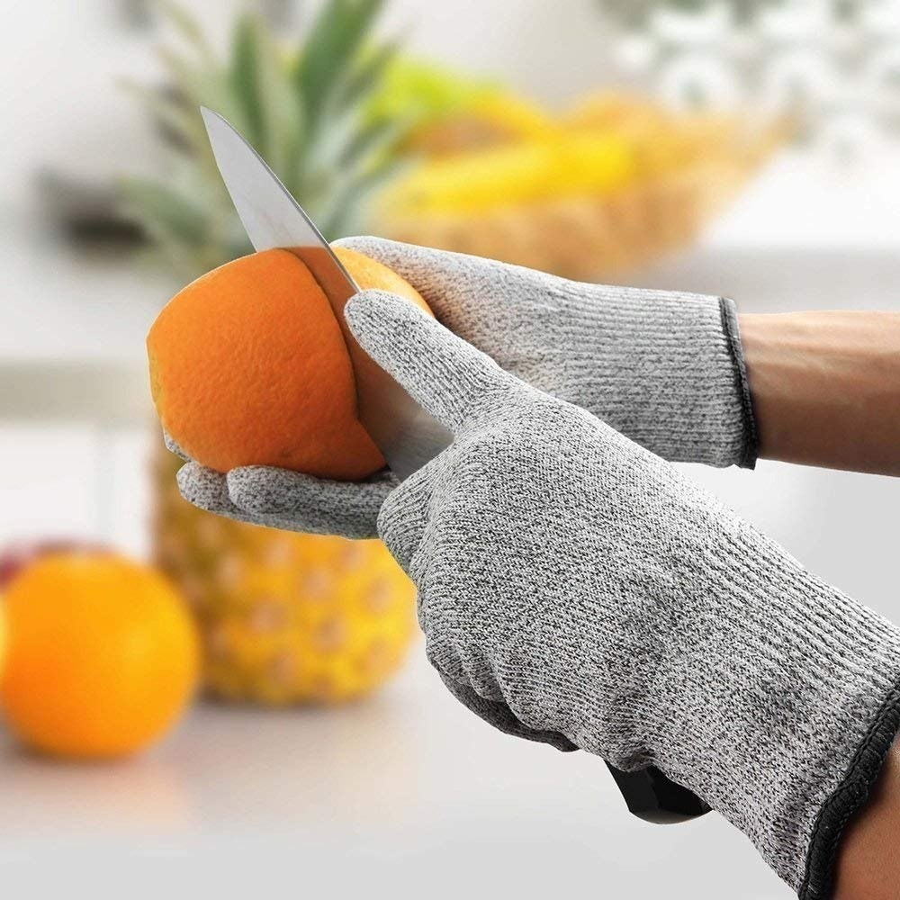 A person chopping an orange wearing the safety gloves.