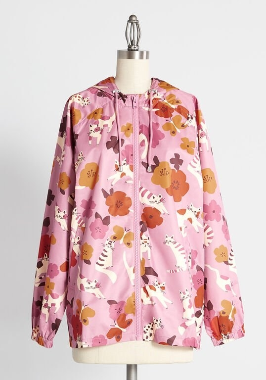 The pink hooded raincoat printed with cream, orange, pink, and mauve cats, flowers, and butterflies