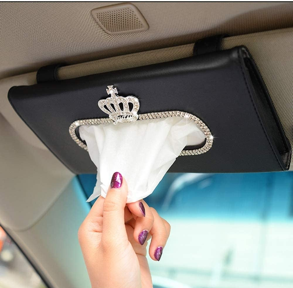 hand pulling tissues out of visor holder that has a rhinestone crown design on it