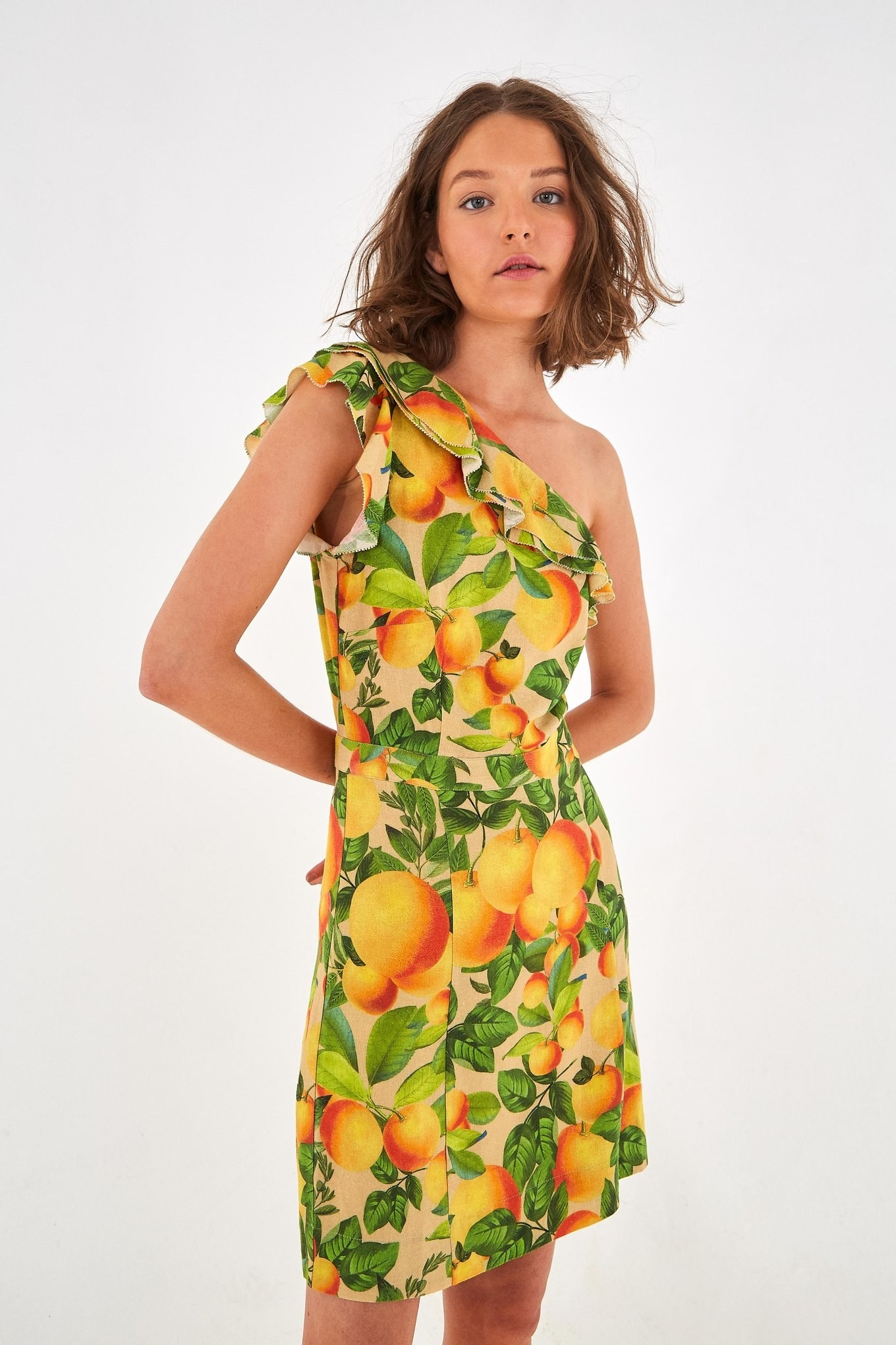a model in the one shouldered short dress cover in a print of oranges and leaves