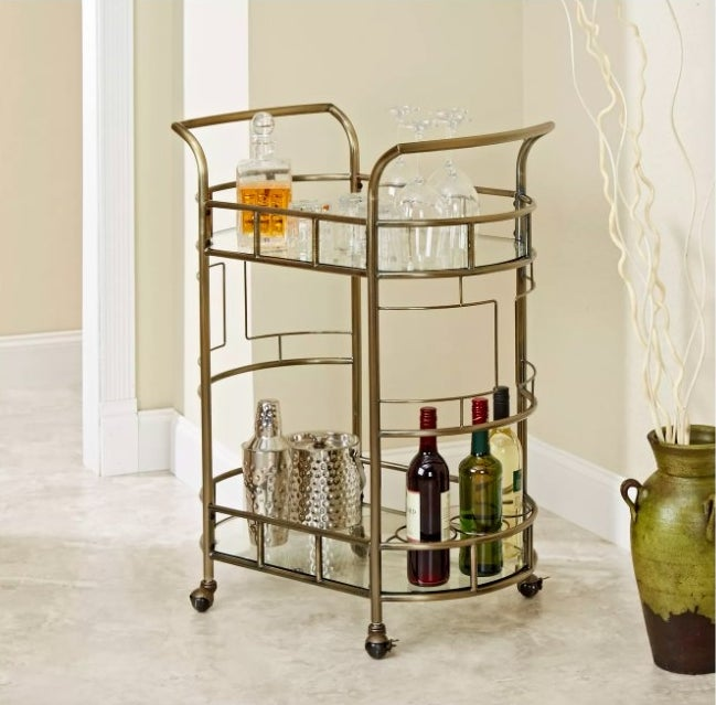 The two-level gold-toned bar cart, with glass shelving on each level, and square, art-deco design between the two levels