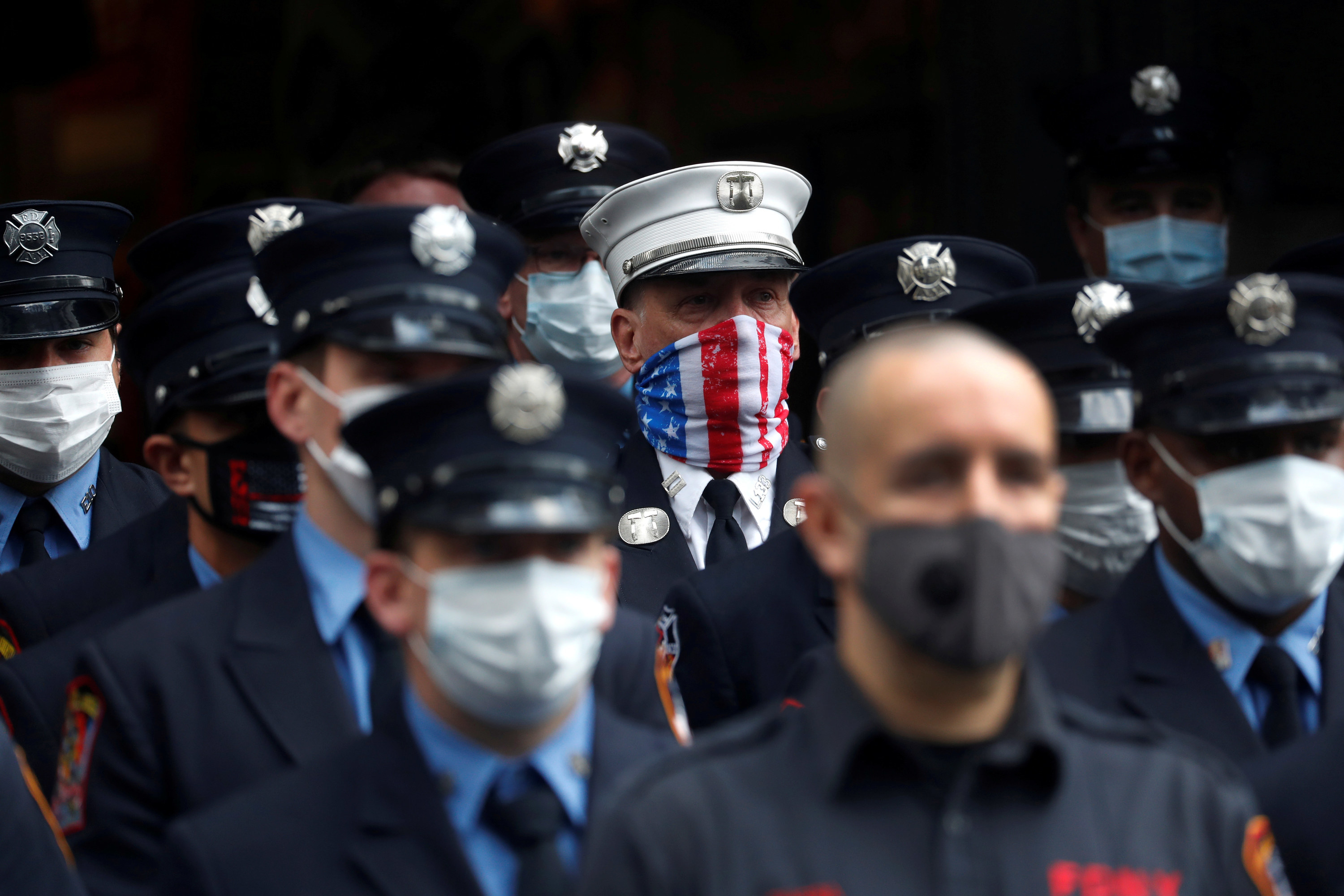 Several uniformed firefighters stand in a row wearing white or gray face masks; in the background one man wears a face mask with a US flag print