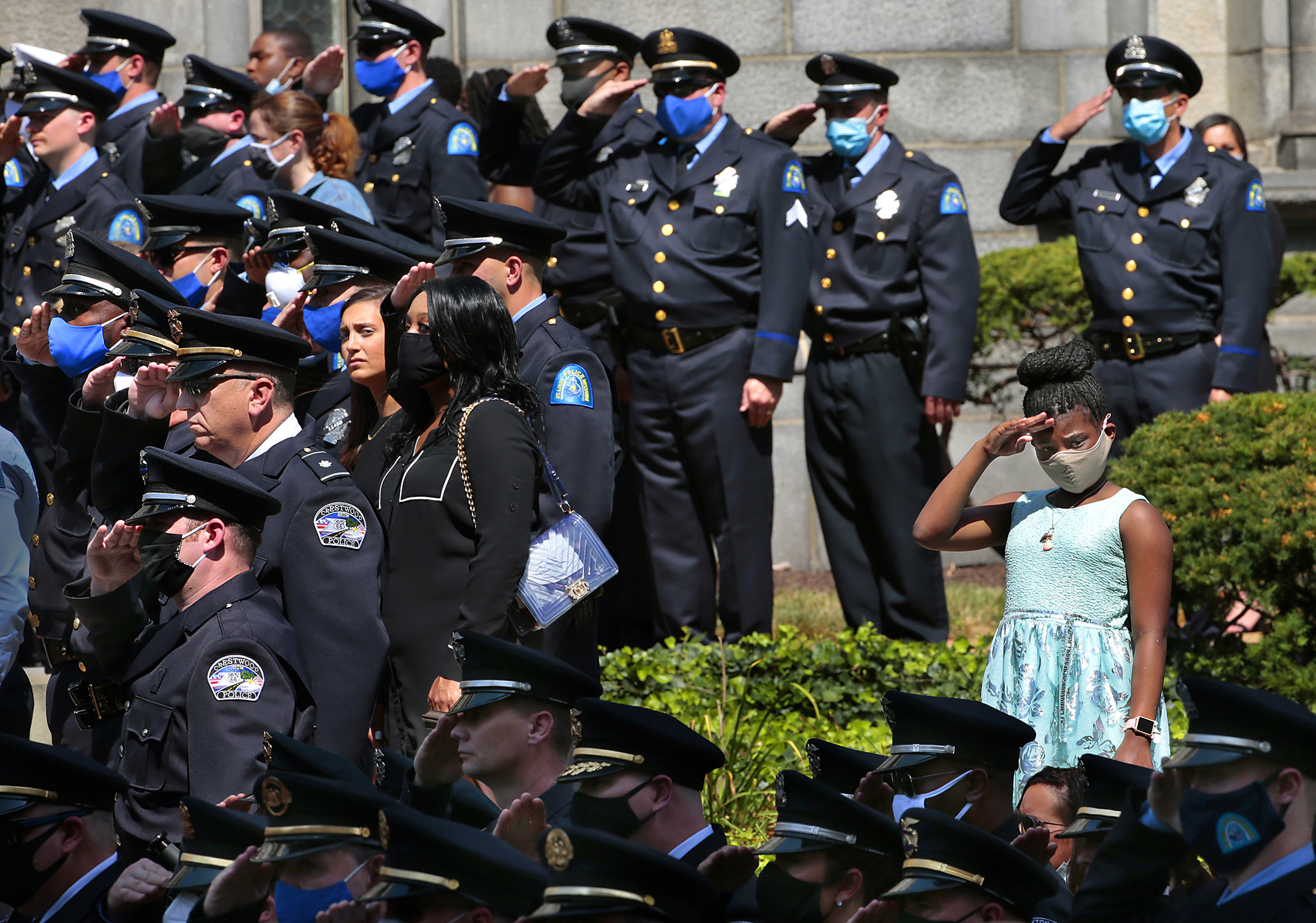 A young girl wearing a face mask and light blue dress salutes with several dozen uniformed police officers around her
