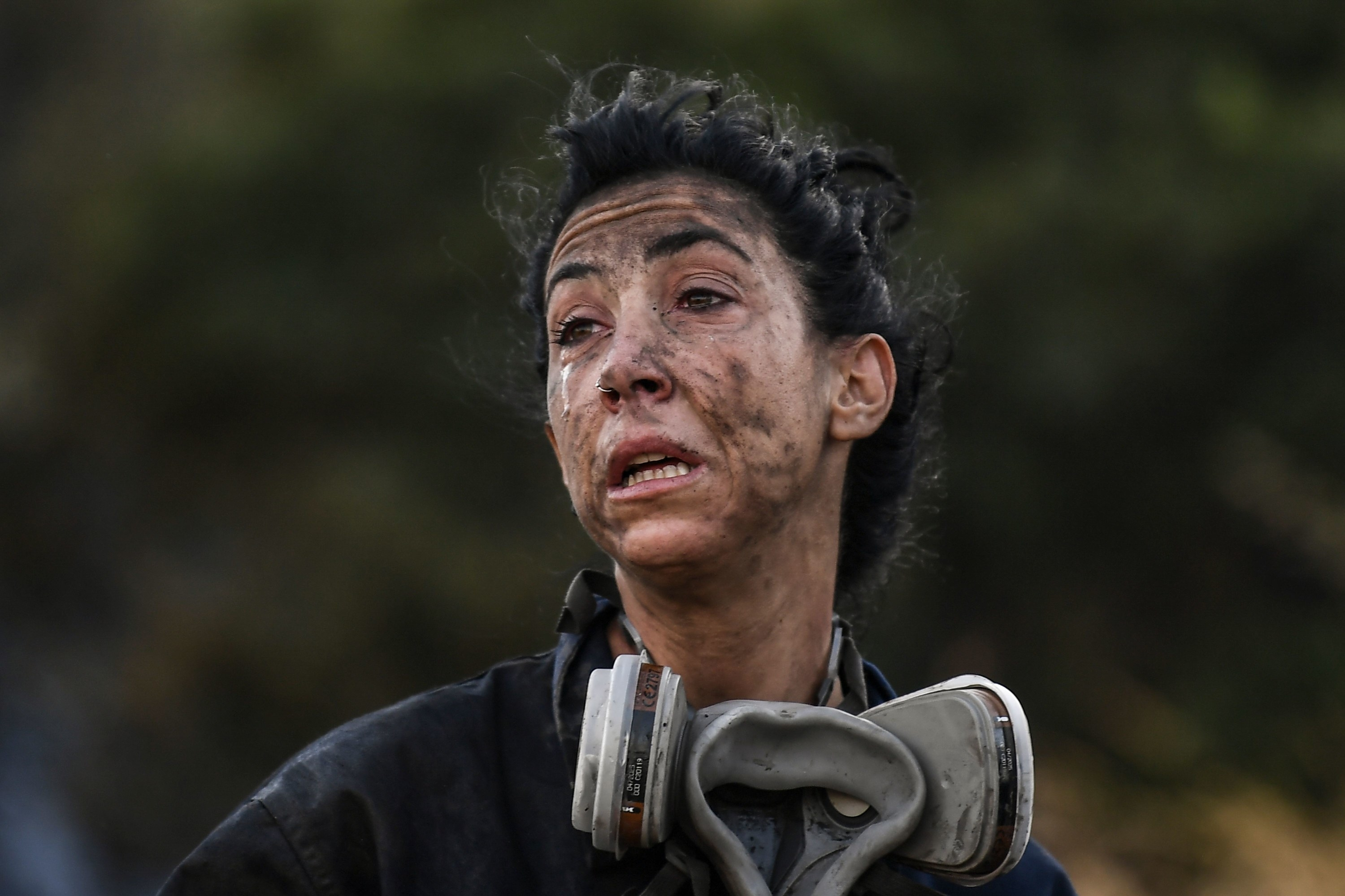 A firefighter with an ash-covered face and a breathing apparatus around her neck grimaces