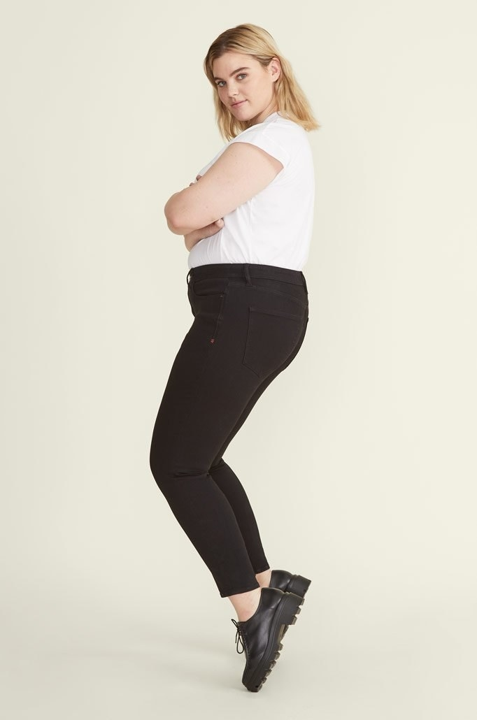 A model in black mid-rise skinny jeans styled with a white t-shirt