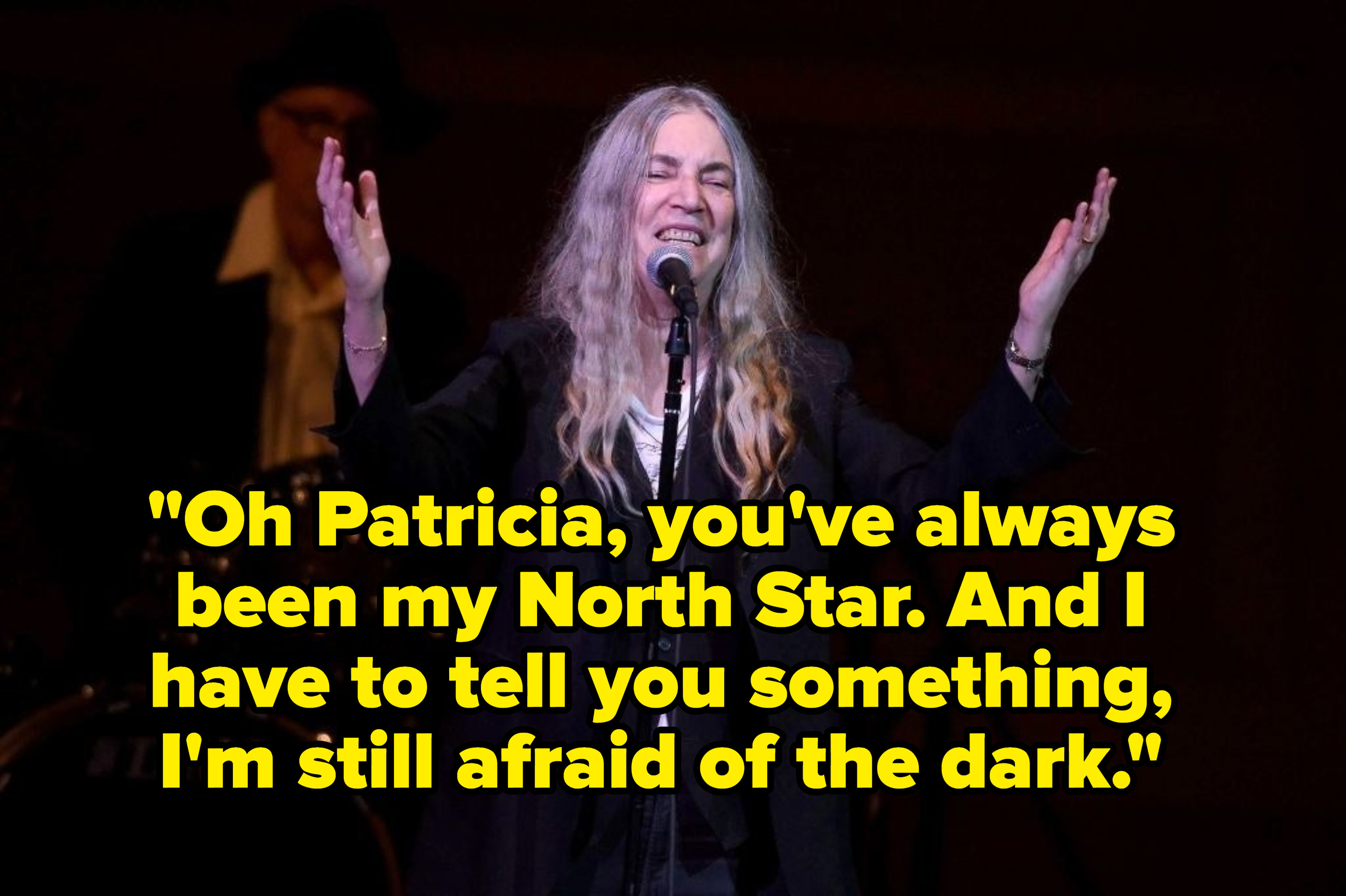 """Patti Smith singing on stage, captioned with the lyric """"Oh Patricia, you've always been my North Star. And I have to tell you something I'm still afraid of the dark."""""""