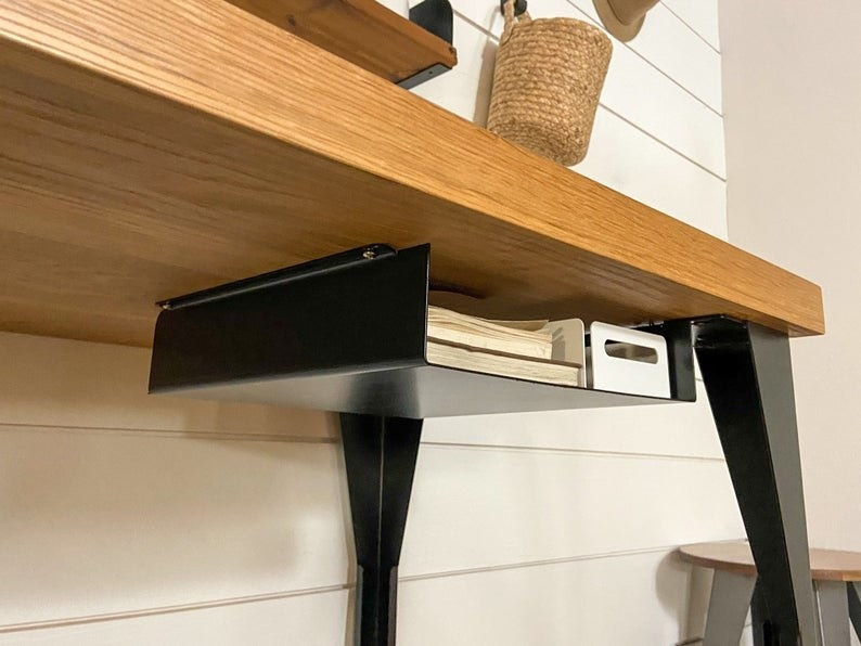 a metal shelf holding books and other items discreetly under a desk