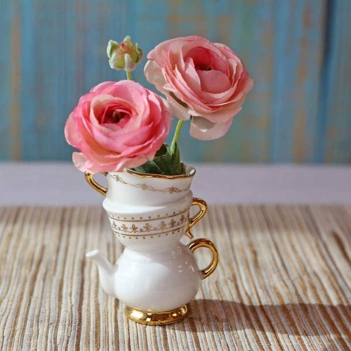 A vase that's shaped like two tea cups on top of a tea pot