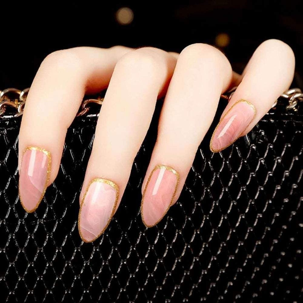 A hand with press-on nails that are marble with gold trim