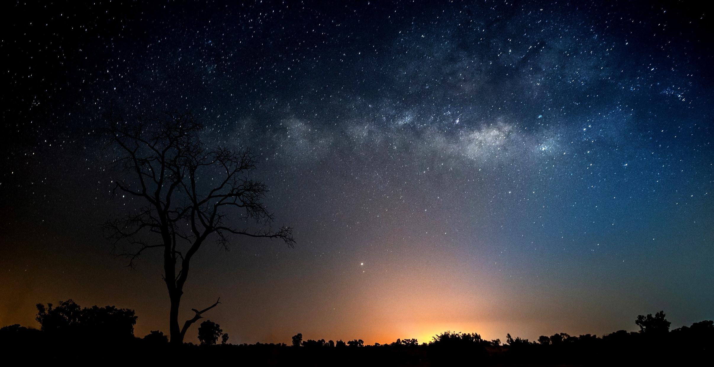 stars shine in a the night sky as the sun tucks beneath the horizon