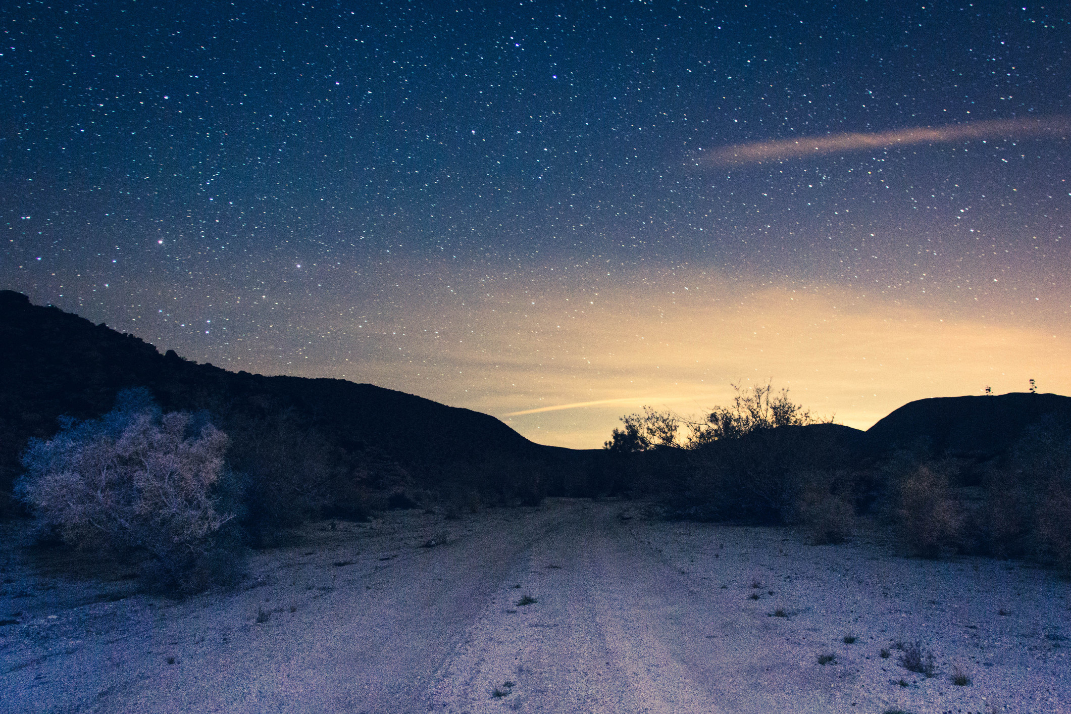 dirt road through the desert at night with stars emerging as the sun sets