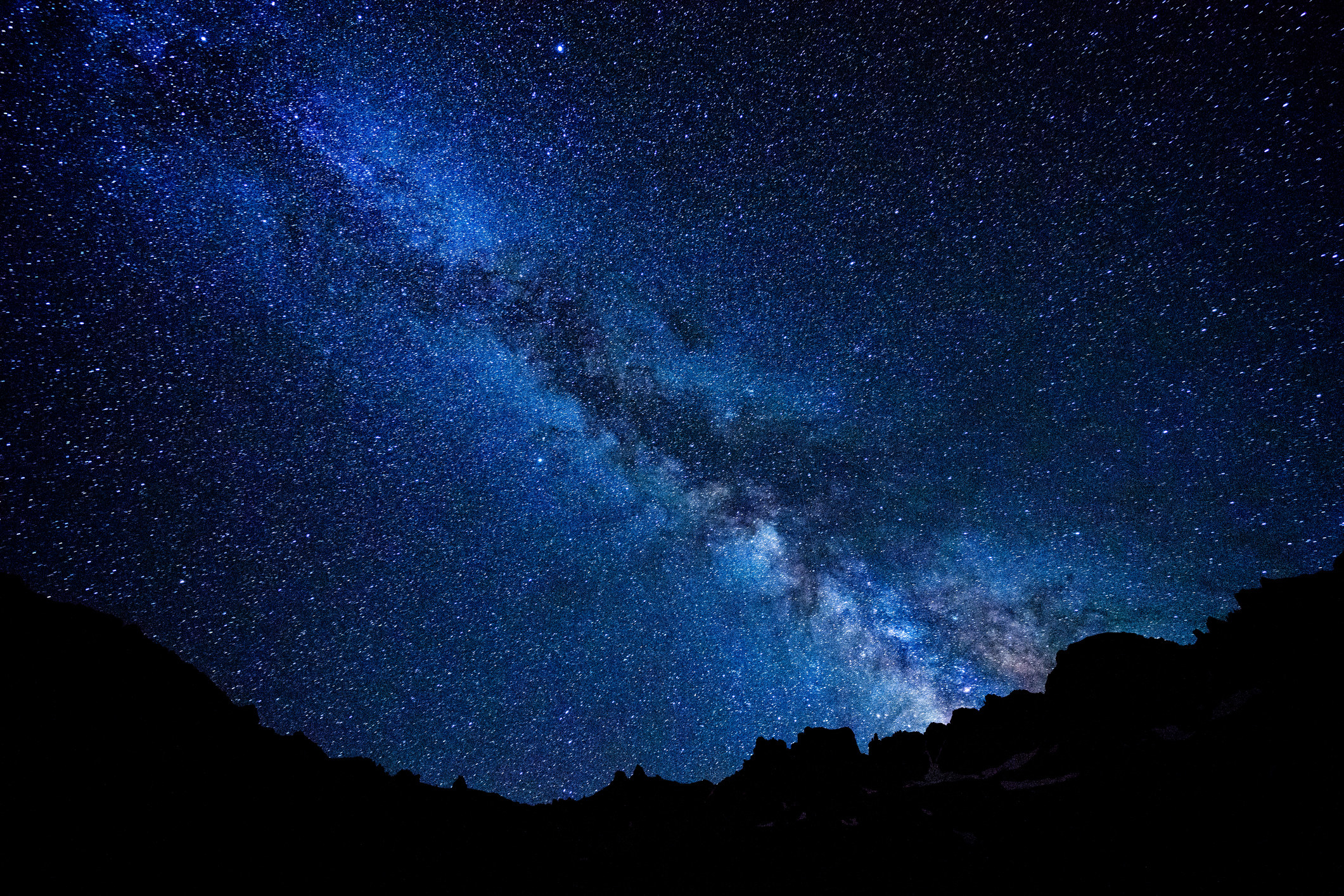 Scenic landscape showing space with stars and the Milky Way with rugged mountain silhouettes