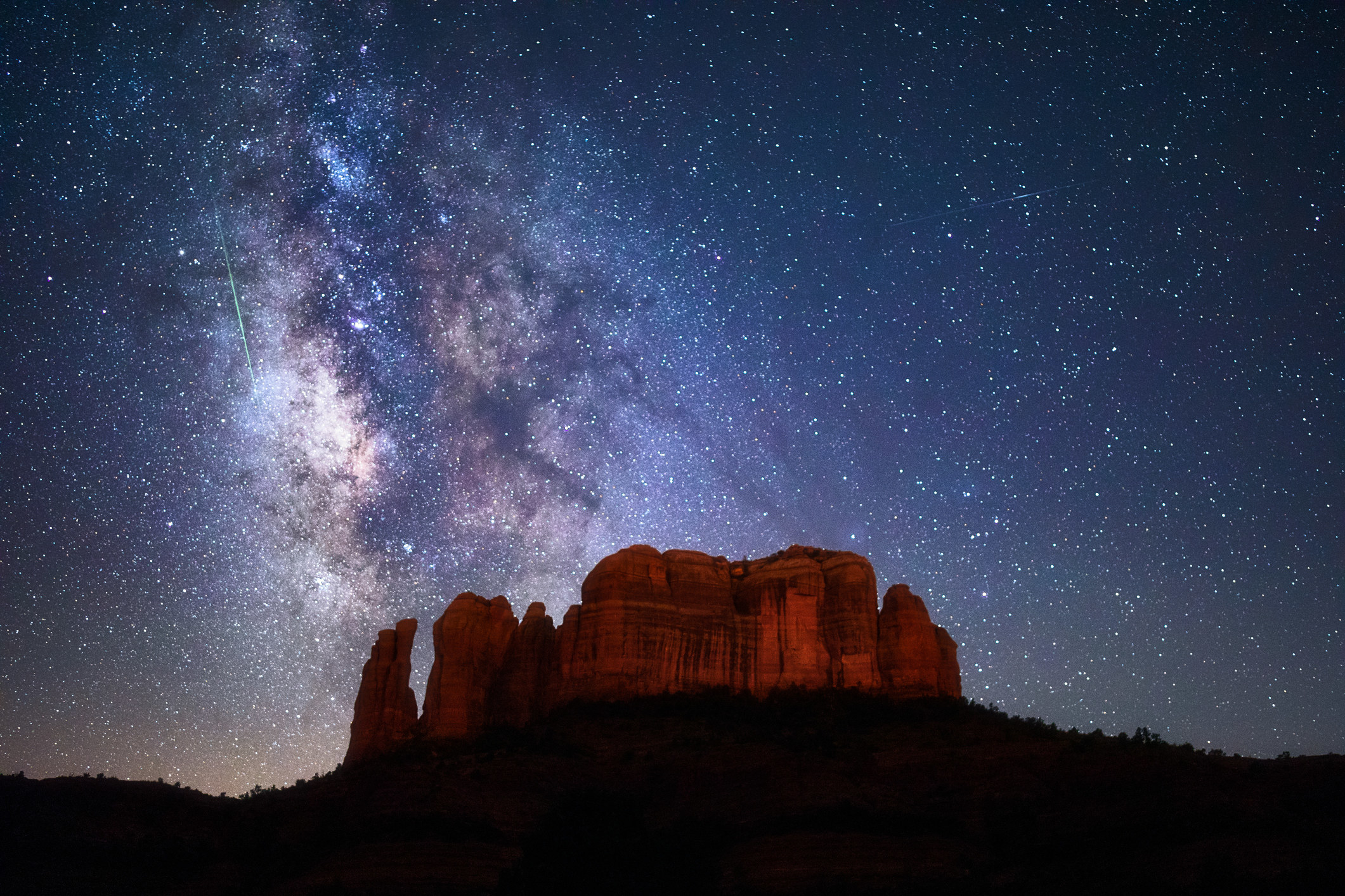 A bright green meteor streaks through the Milky Way and starry night sky above Cathedral Rock in Sedona, Arizona.