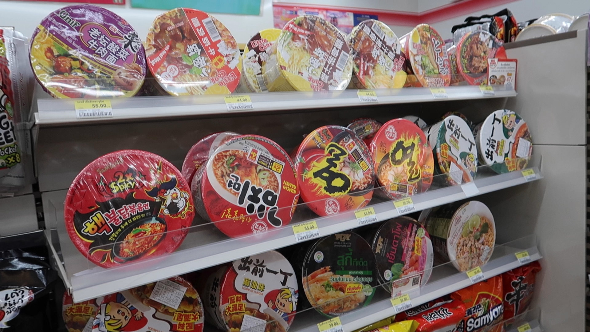 Three shelves full of instant noodle bowls