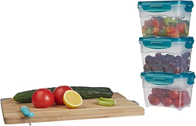 Three meal containers stacked on top of each other with fruits and vegetables in them, next to a cutting board with some tomatoes, limes and cucumbers.