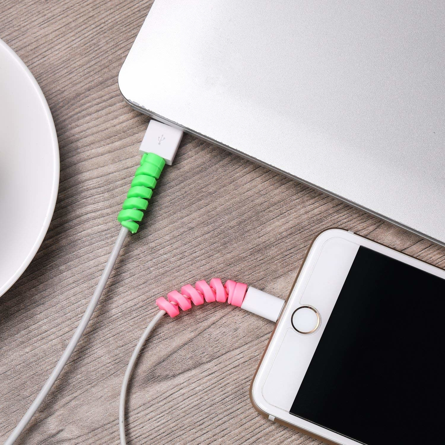 A green charger protector on a cord and a pink on a phone