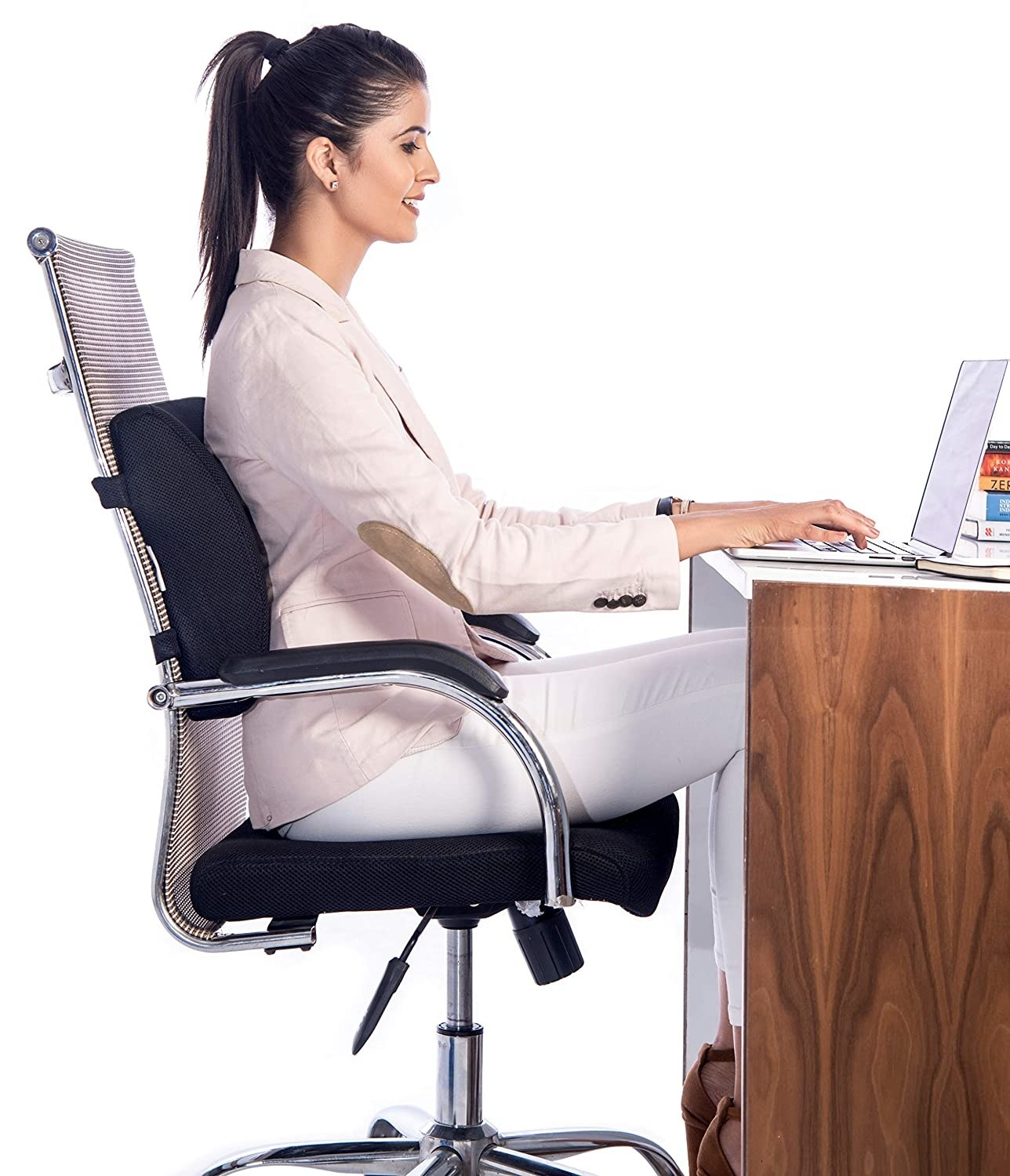 A woman sitting on a chair with back support from the pillow
