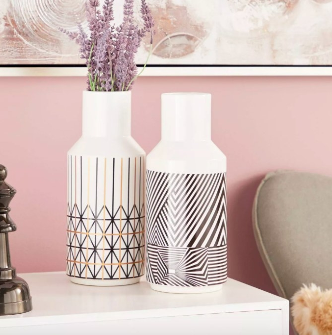 Two tall, milk jug-shaped vases, one with black and gold geometric print, the other with black-and-white op-art swirl pattern