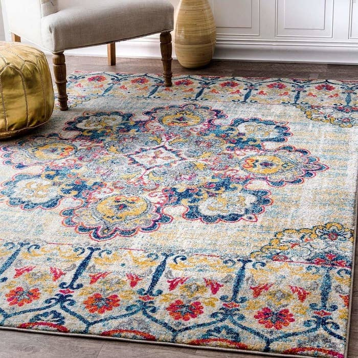 A multi-coloured carpet in shades of cream, blue, red, and yellow.