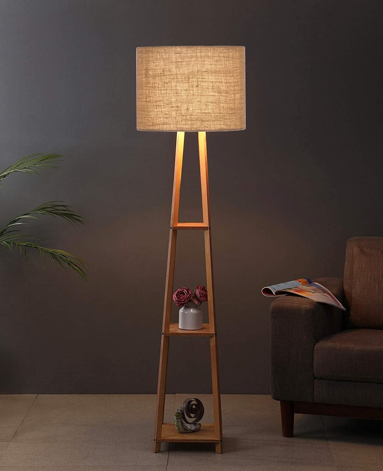 A 3-tired lamp with plants and showpieces on its shelves.