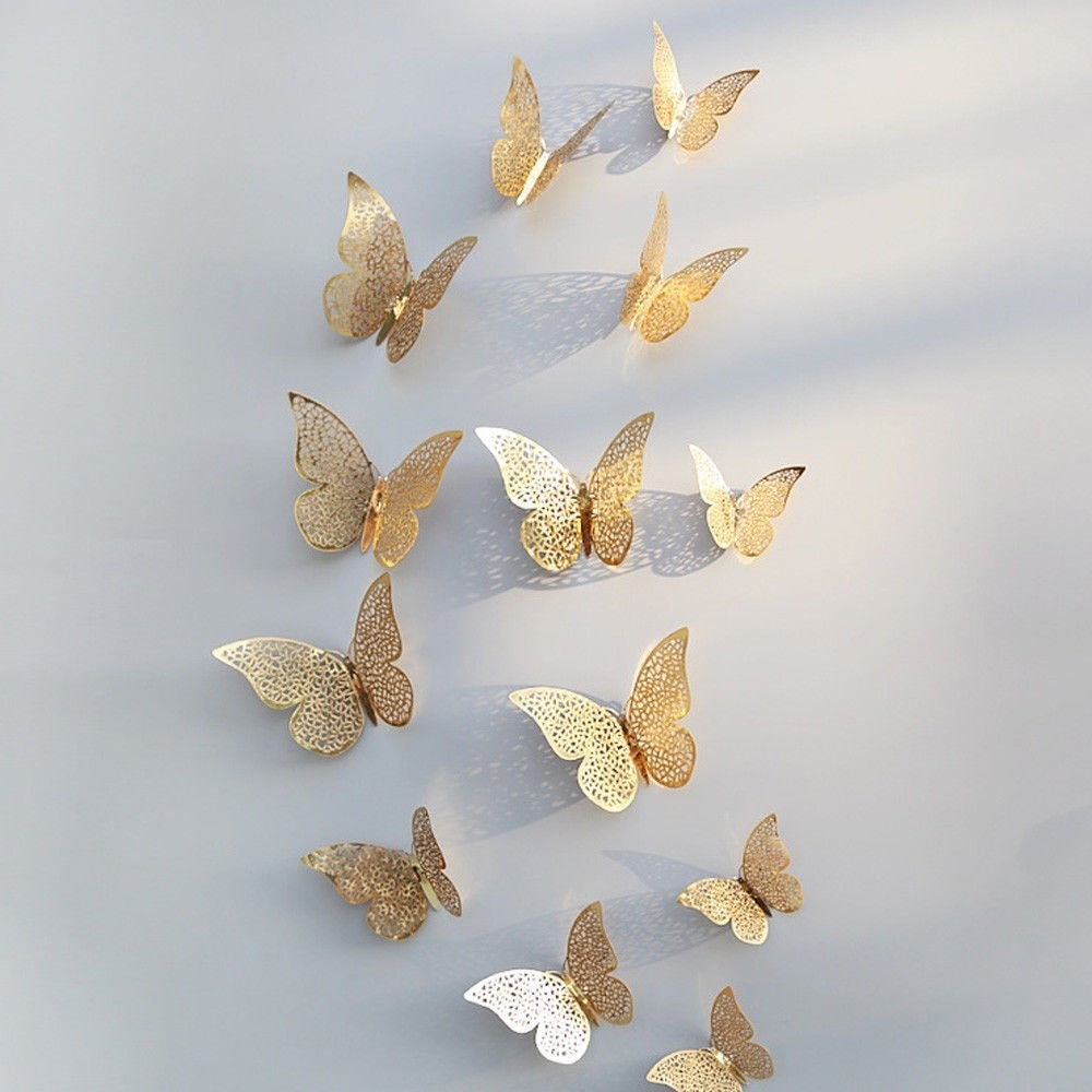 Golden butterflies stuck on a wall.