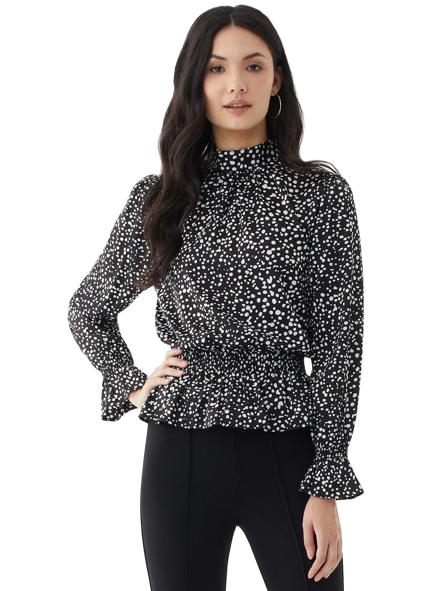 Model wears peplum top in black abstract dot