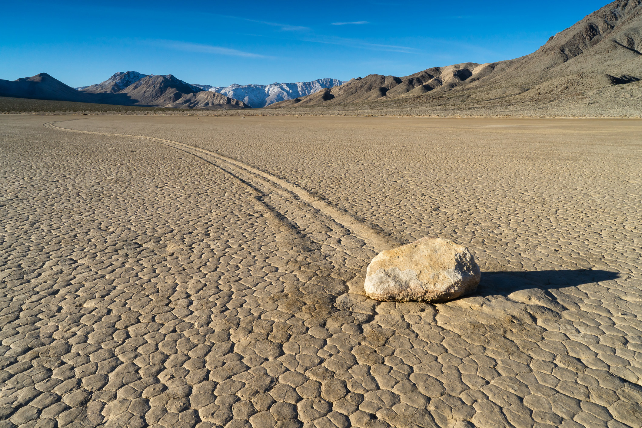 A desert setting with a moving rock's imprints in the ground.